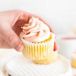 hand picking up rhubarb cupcake