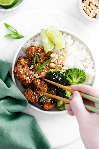 air fryer sesame chicken in bowl with chopsticks