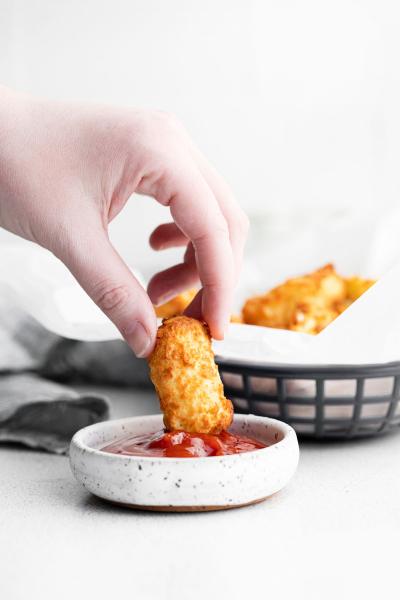 hand dipping tater tot in ketchup