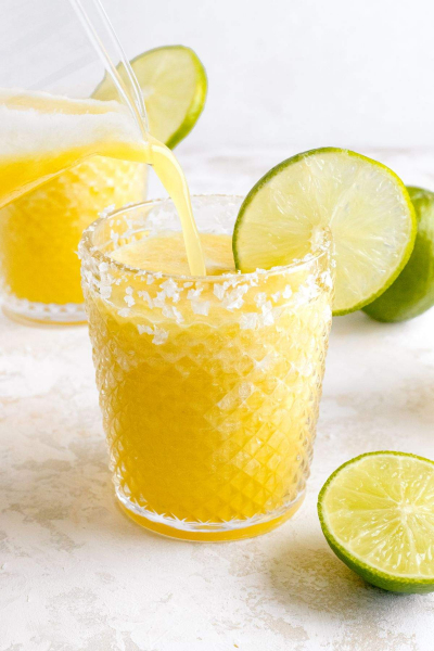 pineapple margarita being poured into glass