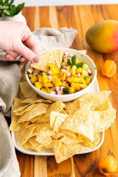 hand dipping chip in mango habanero salsa