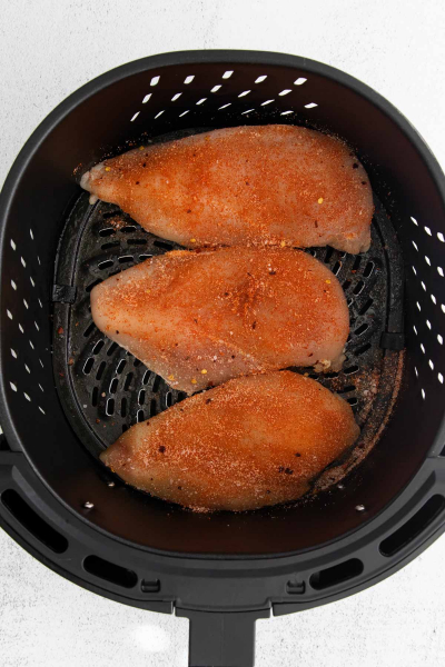 raw chicken breast in air fryer basket