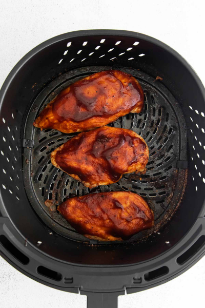 chicken breast in air fryer basket with bbq sauce rubbed over it